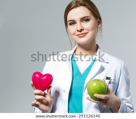 Beautiful smiling female doctor holding red heart and green apple in front of chest. Health life and wholesome food concept. Vegetarian lifestyle concept. Cardiology concept  - stock photo