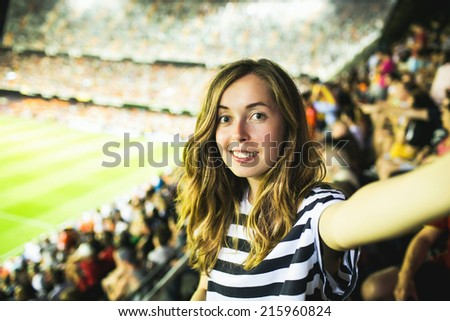 Beautiful smiling female football supporter watching football game and making selfie self-portrait with smartphone at Camp Nou Stadium in Barcelona, Spain - stock photo