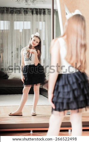 Beautiful smiling girl combing her hair in front of the mirror - stock photo
