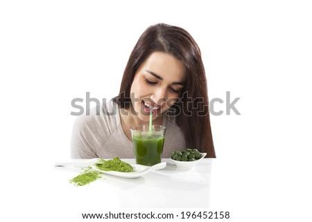Beautiful smiling girl drinking green drink. Spirulina, chlorella and wheatgrass. Healthy lifestyle, detox. - stock photo