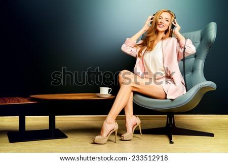 Beautiful smiling girl enjoying listening to music in headphones. Interior, furniture. Leisure. - stock photo