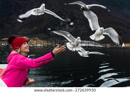 Beautiful smiling girl feeding the seagulls from the ship in Norway. - stock photo