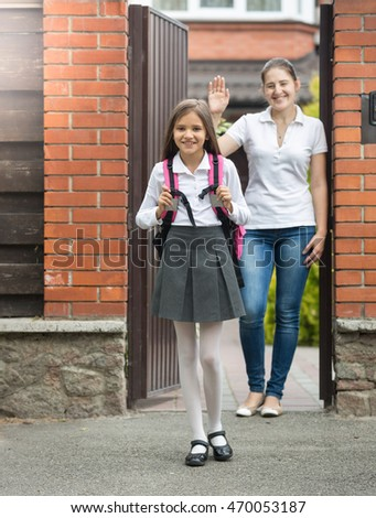 Beautiful smiling girl going out the house to school. Mother standing in doorway and waving to her