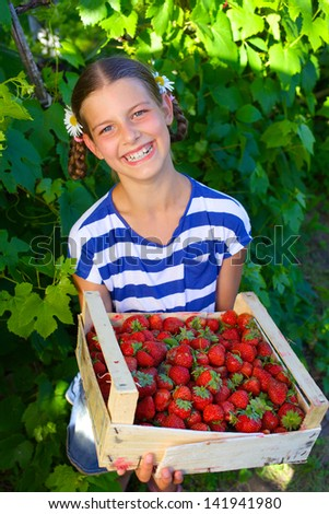 Beautiful smiling girl holding a box of strawberries in garden