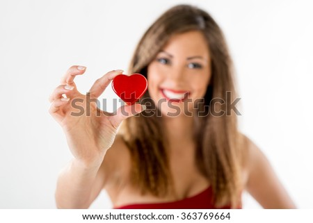 Beautiful smiling girl holding a red heart. Selective focus. Focus on the heart.