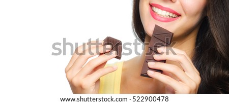 Beautiful smiling girl holding and eating chocolate isolated on white background.