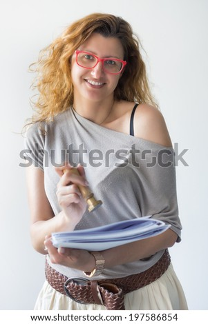 beautiful smiling girl holding business documents, folders and ink stamp on white background - stock photo
