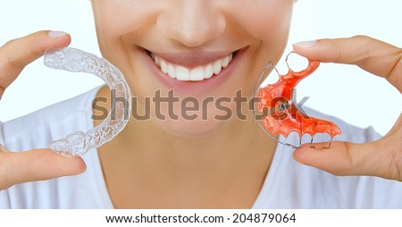Beautiful smiling girl holding retainer for teeth (dental braces) and individual tooth tray - stock photo