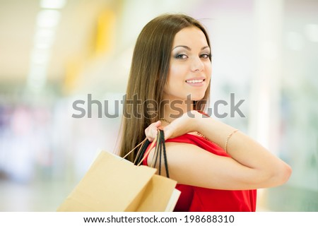 Beautiful smiling girl in a red dress with long hair shopping, holding shopping bags
