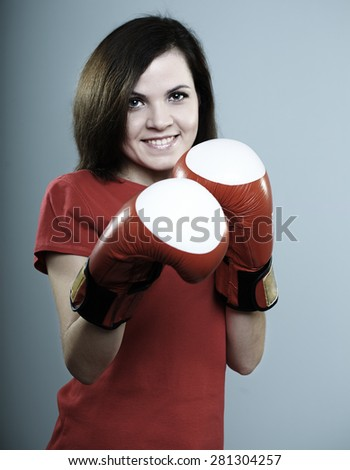 beautiful smiling girl in a red shirt and red boxing gloves on a gray background