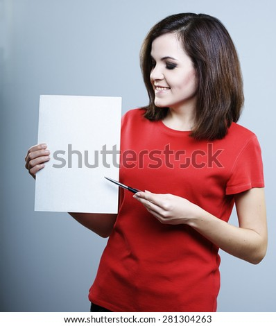 beautiful smiling girl in a red shirt holding a poster and pen in the other hand and shows him