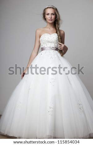 beautiful smiling girl in a white wedding dress on a gray background - stock photo