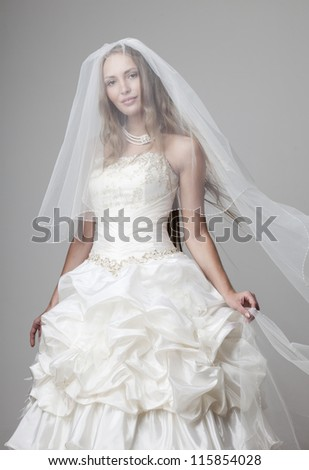 beautiful smiling girl in a white wedding dress with a veil on a gray background