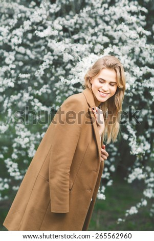 Beautiful smiling girl in blossom garden on a spring day - stock photo