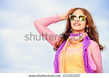 Beautiful smiling girl in bright clothes standing outdoors in a sunny summer day.