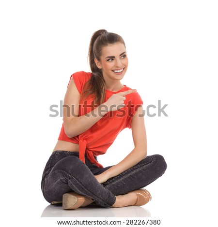 Beautiful smiling girl in red top, black jeans is sitting on the floor with legs crossed, pointing and looking away. Full length studio shot isolated on white. - stock photo
