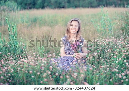 Beautiful smiling girl in the blossom field - stock photo