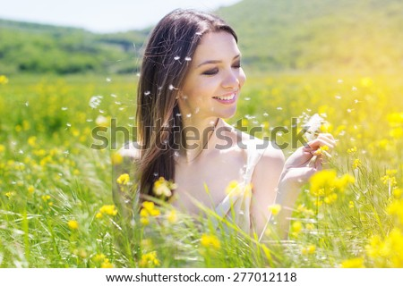 Beautiful smiling girl is holding dandelion in the field of yellow flowers is wearing flying white wedding dress - stock photo