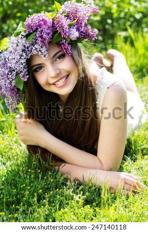 Beautiful smiling girl is resting in park with fashion makeup is wearing beautiful wreath of lilac flowers - stock photo