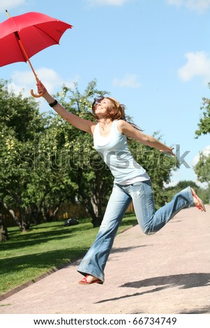 beautiful smiling girl jumping with red umbrella and copy-space