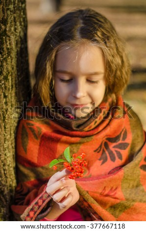 Beautiful smiling girl looking at rowanberry
