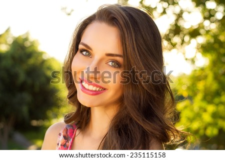 beautiful smiling girl looking at you against spring green bokeh background - stock photo