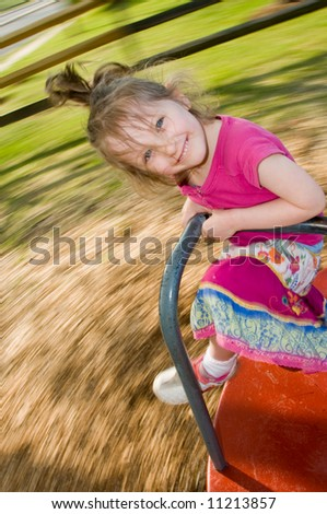 beautiful smiling girl rides a merry-go-round in motion
