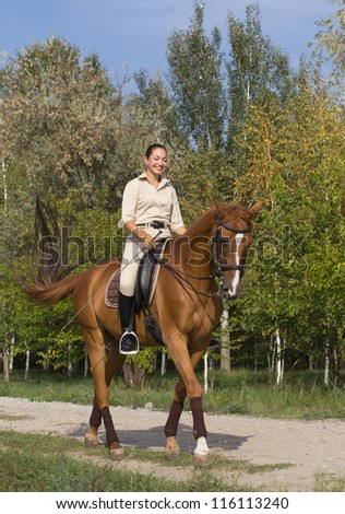 Beautiful smiling girl riding a brown horse through woodland