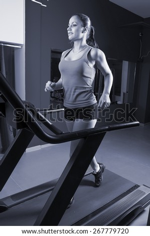 Beautiful smiling girl running on treadmill in the gym. - stock photo