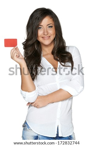 Beautiful smiling girl showing red card in hand, over white background - stock photo