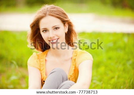Beautiful smiling girl sits on green lawn in city park. - stock photo