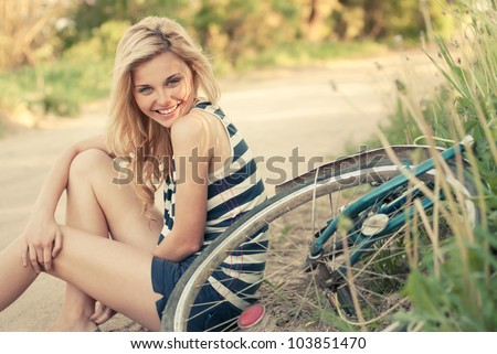 beautiful smiling girl sitting next to bike - stock photo