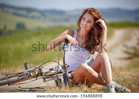 beautiful smiling girl sitting next to bike, summer time - stock photo