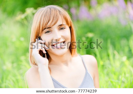 Beautiful smiling girl speaks by mobile phone against summer green nature. - stock photo