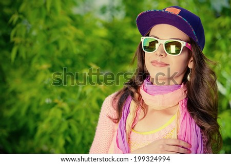 Beautiful smiling girl teenager in bright clothes standing outdoors in a sunny summer day.