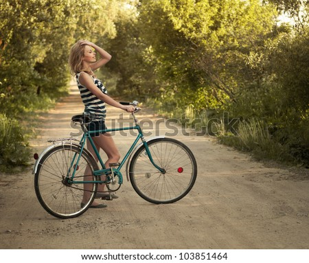 beautiful smiling girl with a bicycle on the road - stock photo