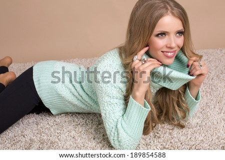 beautiful smiling girl with blond hair in sweater lying on carpet in studio - stock photo
