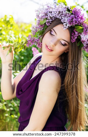 Beautiful smiling girl with fashion makeup is wearing beautiful wreath of purple lilac flowers - stock photo