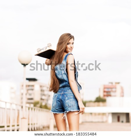 beautiful smiling girl with long legs in jeans short overalls stands with skateboard on shoulder - stock photo
