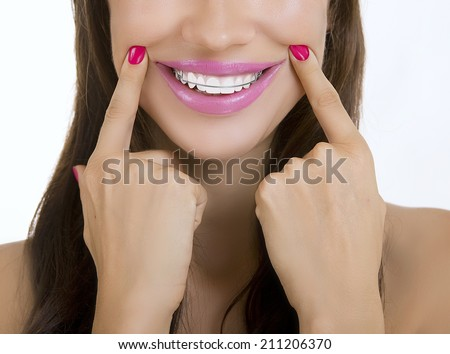 Beautiful smiling girl with retainer for teeth, blue background - stock photo