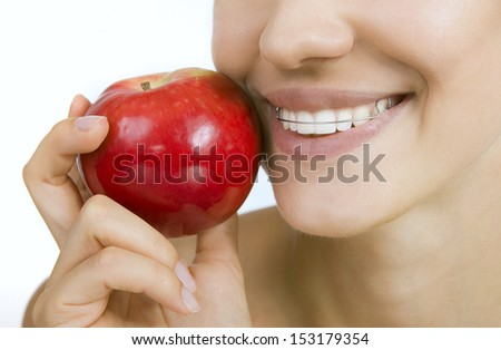 Beautiful smiling girl with retainer for teeth - healthy teeth and apple - stock photo