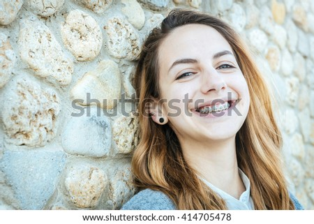Beautiful smiling girl with retainer for teeth is resting on the outdoors . - stock photo
