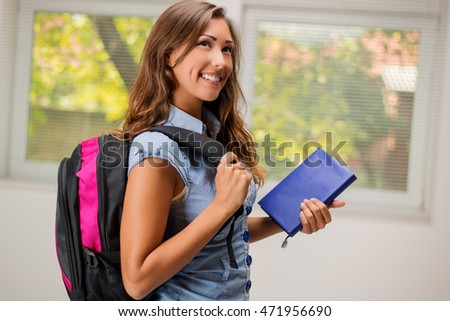 Beautiful smiling girl with school bag and book.