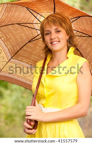Beautiful smiling girl with sun-protection umbrella against summer nature. - stock photo