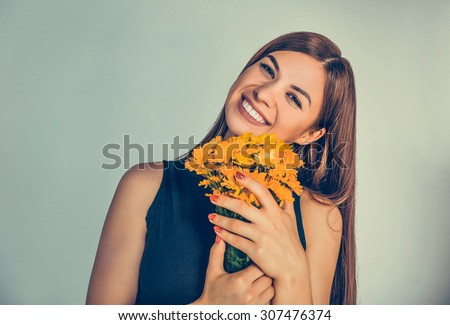 Beautiful smiling girl, woman holding bouquet of marigold, calendula. Young smiley cute female lady smelling flowers isolated on green background wall. Positive facial expression human emotion feeling - stock photo