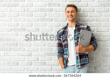 Beautiful smiling guy standing against the background of a white wall with a laptop in hand, looking camera - stock photo
