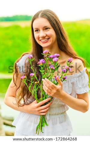beautiful smiling happy girl with a bouquet - stock photo