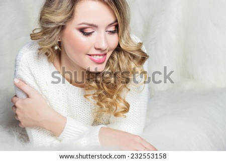 beautiful smiling happy girl with bright makeup lies on the bed with fur in white sweater - stock photo