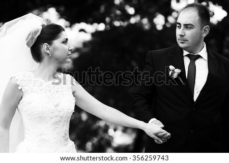 Beautiful smiling happy young couple kissing  on the street on their wedding day, close up portrait