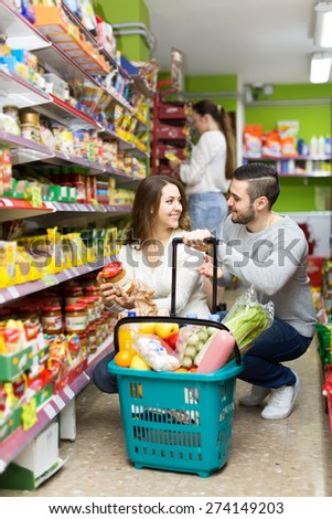 Beautiful smiling heterosexual couple buying healthy food at a supermarket